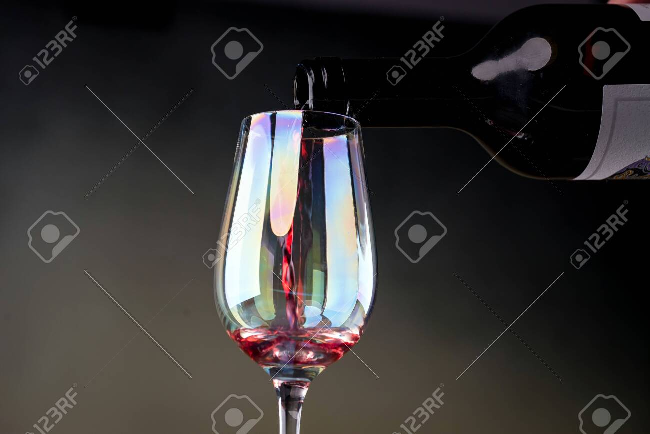Red wine being poured into a glass close-up - 142548090