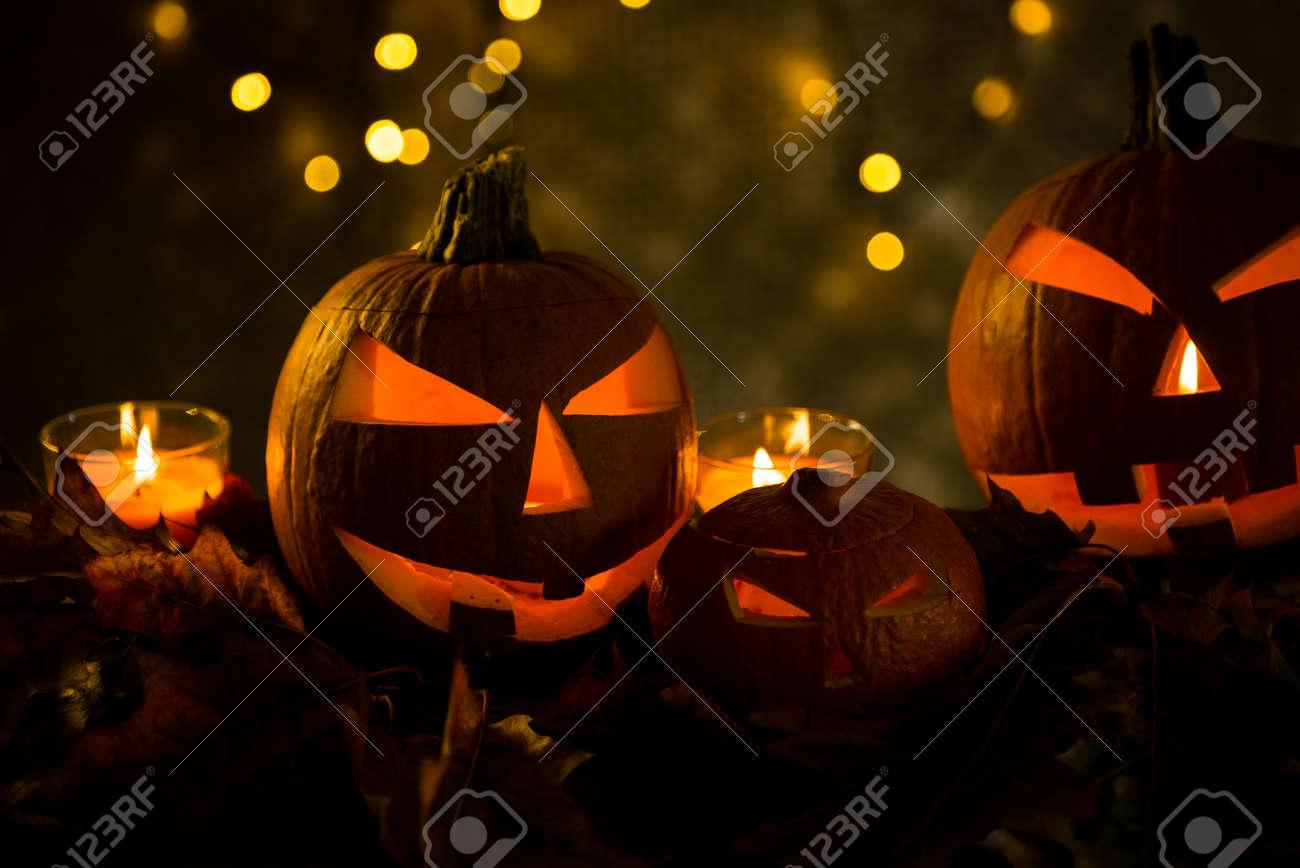 Halloween pumpkin head jack lantern with burning candles in scary deep night - 141470952