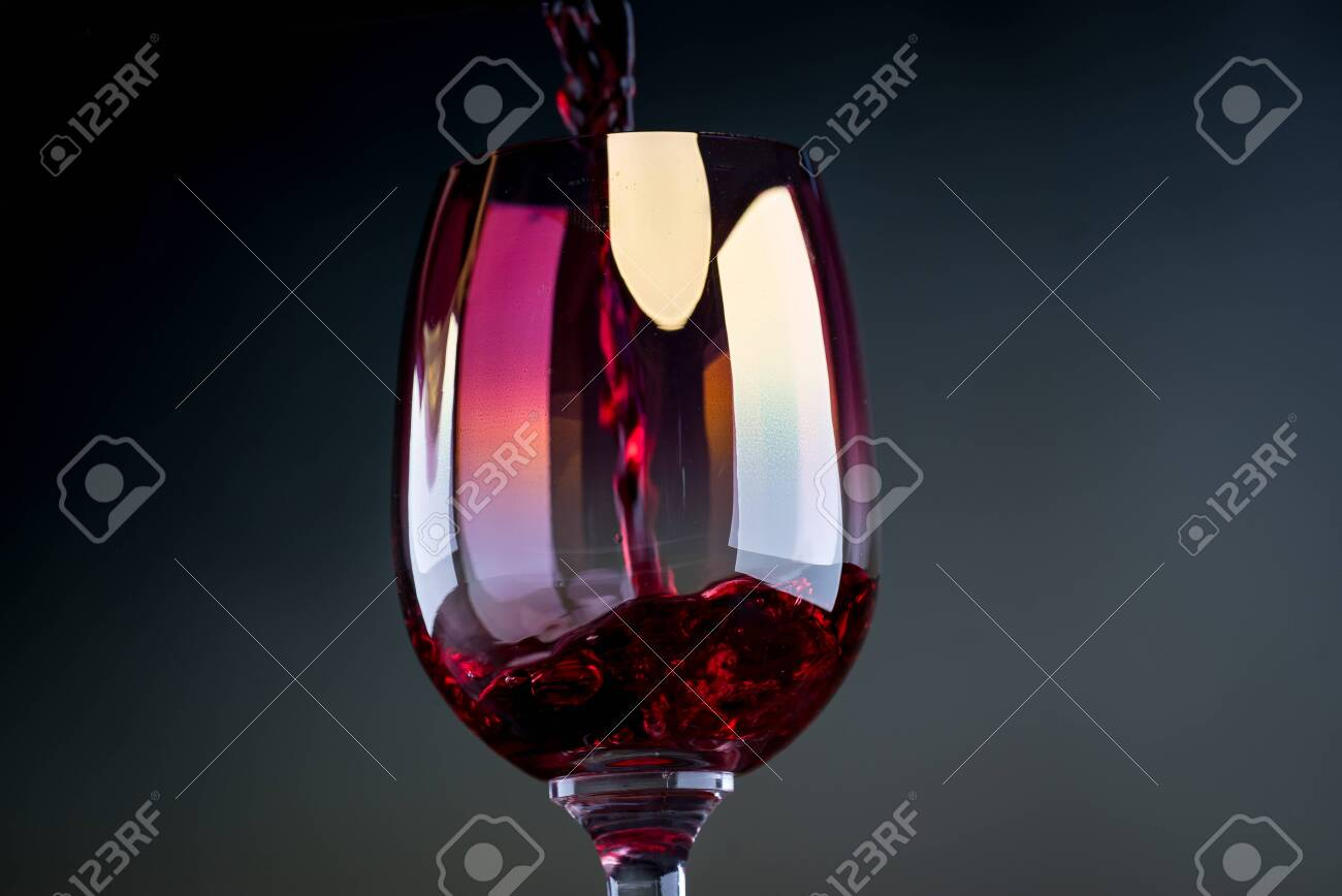 Red wine being poured into a glass close-up - 142548092