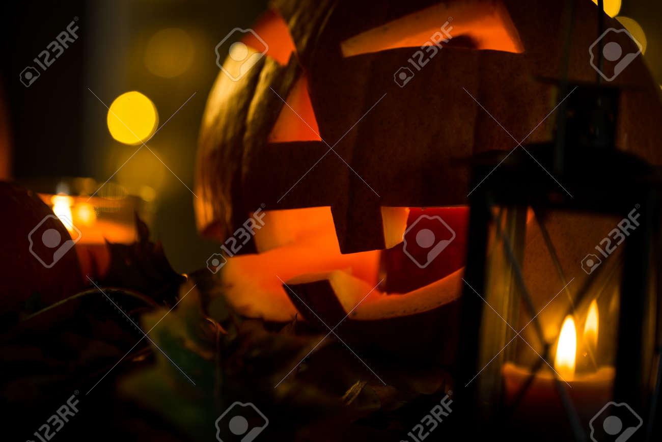 Halloween pumpkin head jack lantern with burning candles in scary deep night - 141471137