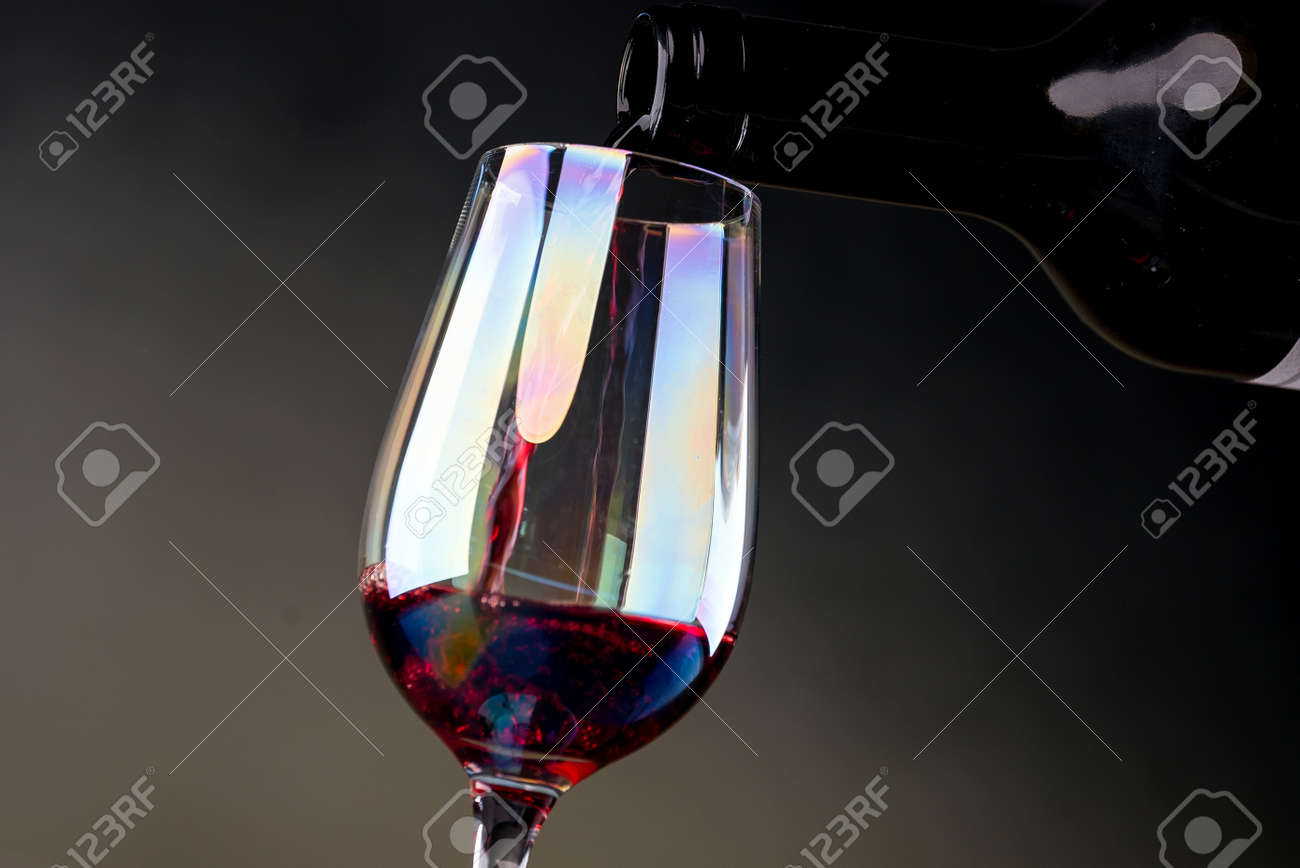 Red wine being poured into a glass close-up - 142548099