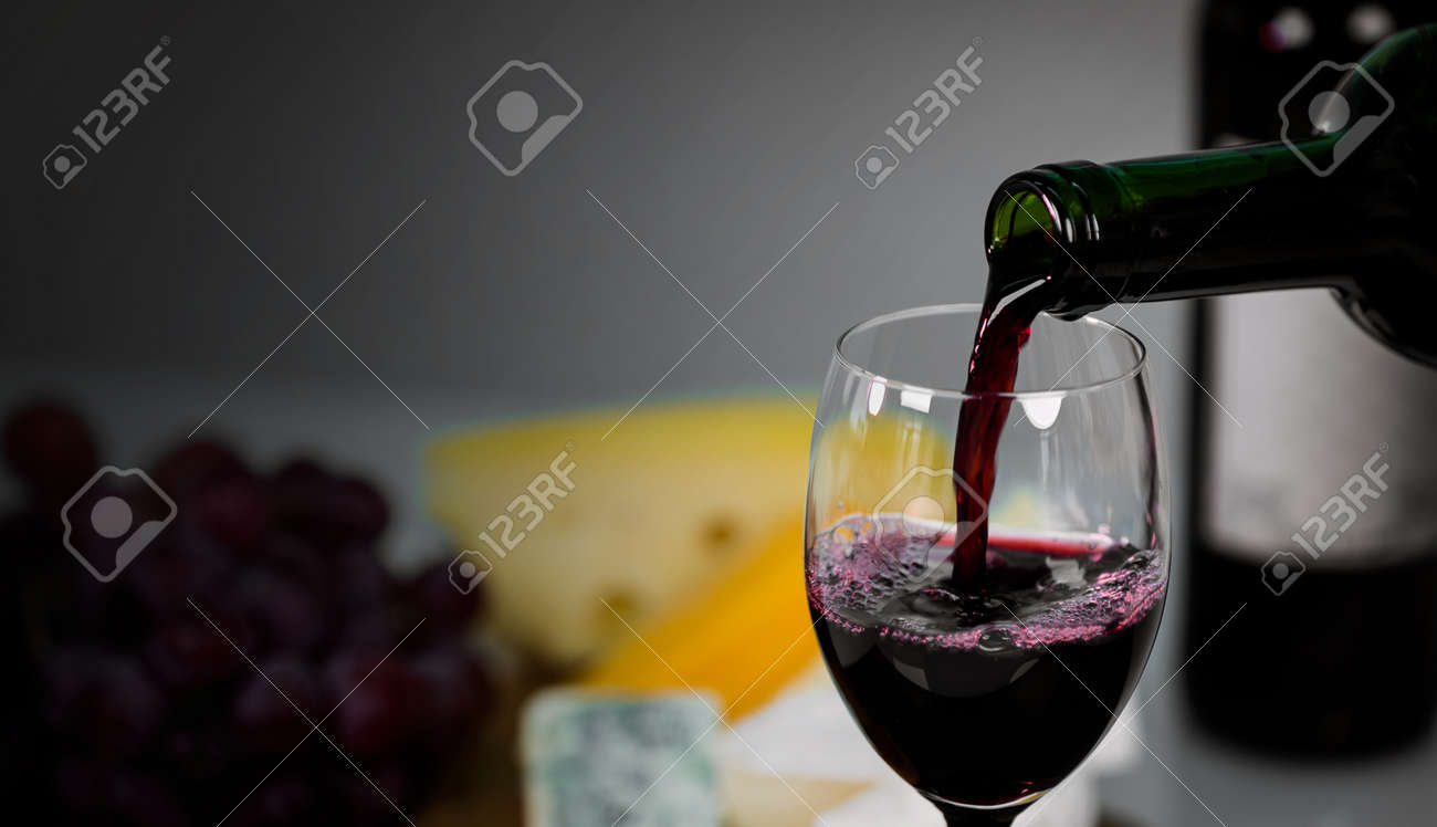 Red wine being poured into a glass close-up - 142548101
