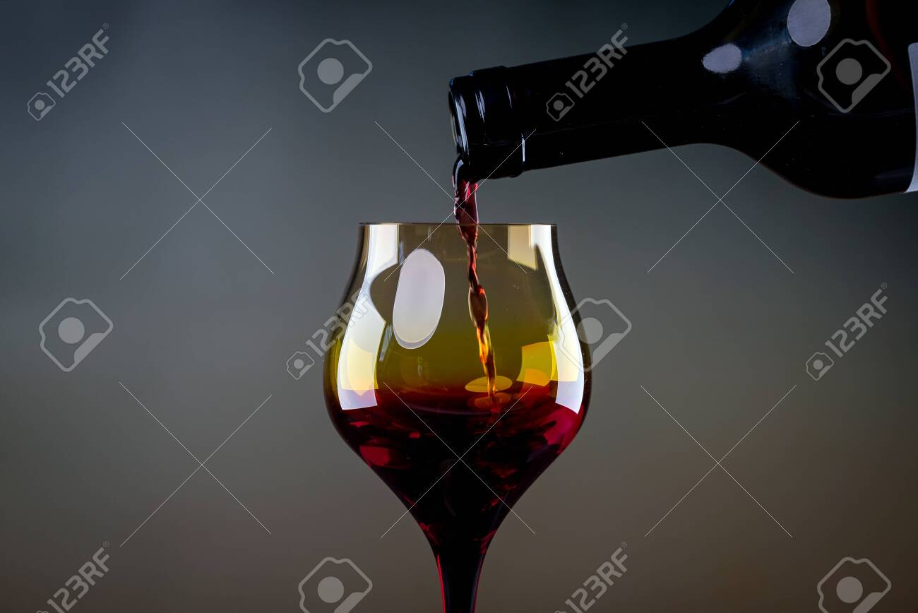 Red wine being poured into a glass close-up - 142547859
