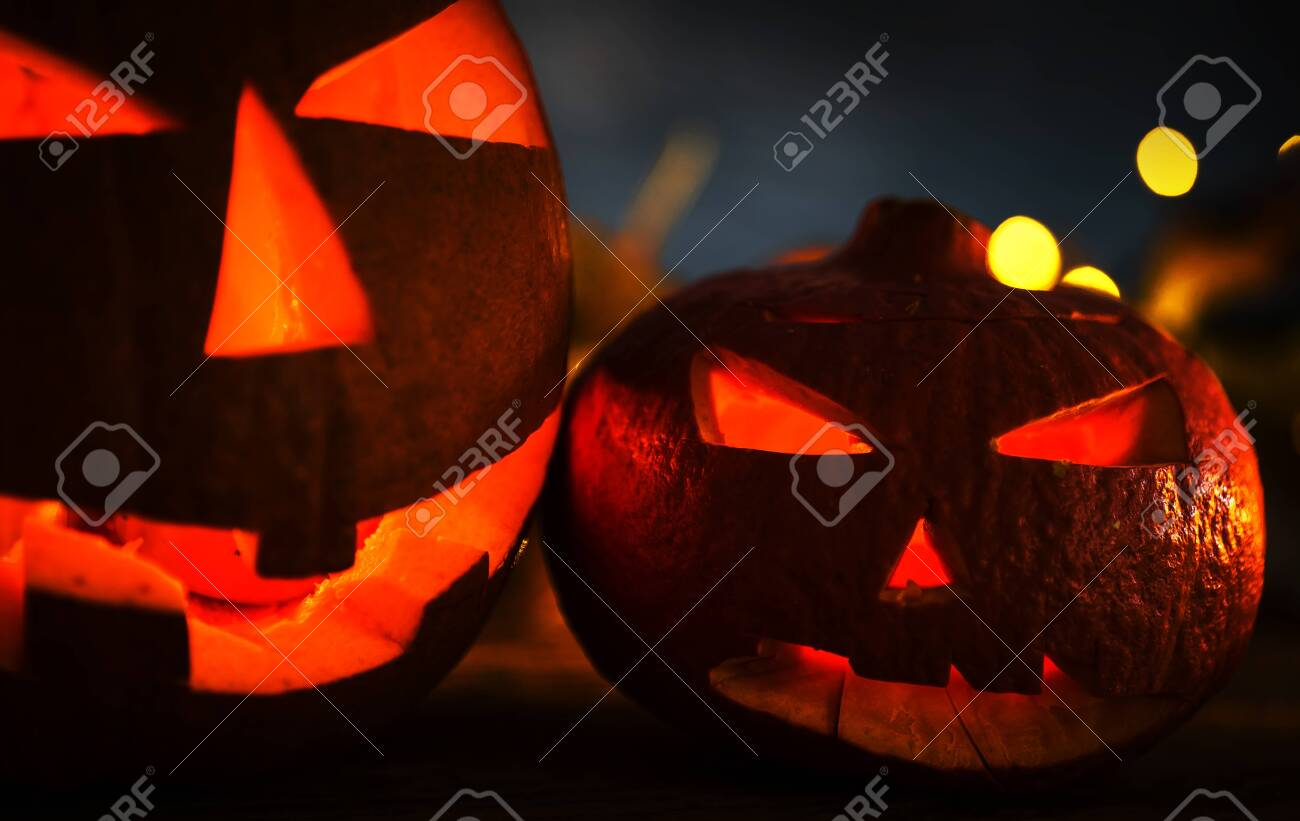 Halloween pumpkin head jack lantern with burning candles in scary deep night - 141471257