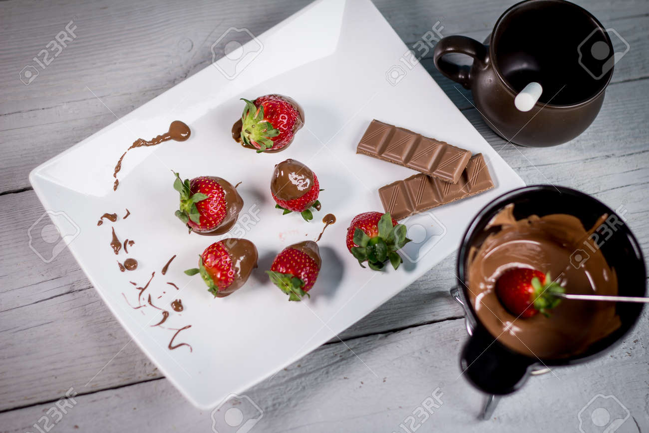 Dipping fresh fruits into pot with tasty chocolate fondue - 142547858