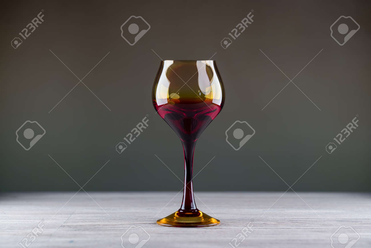 Pouring red wine from a bottle into a wineglass: wine tasting and celebration - 144316198