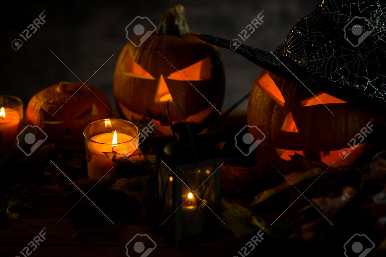 Halloween pumpkin head jack lantern with burning candles in scary deep night - 141471261