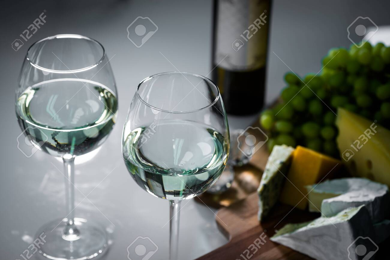 Pouring red wine from a bottle into a wineglass: wine tasting and celebration - 144316208