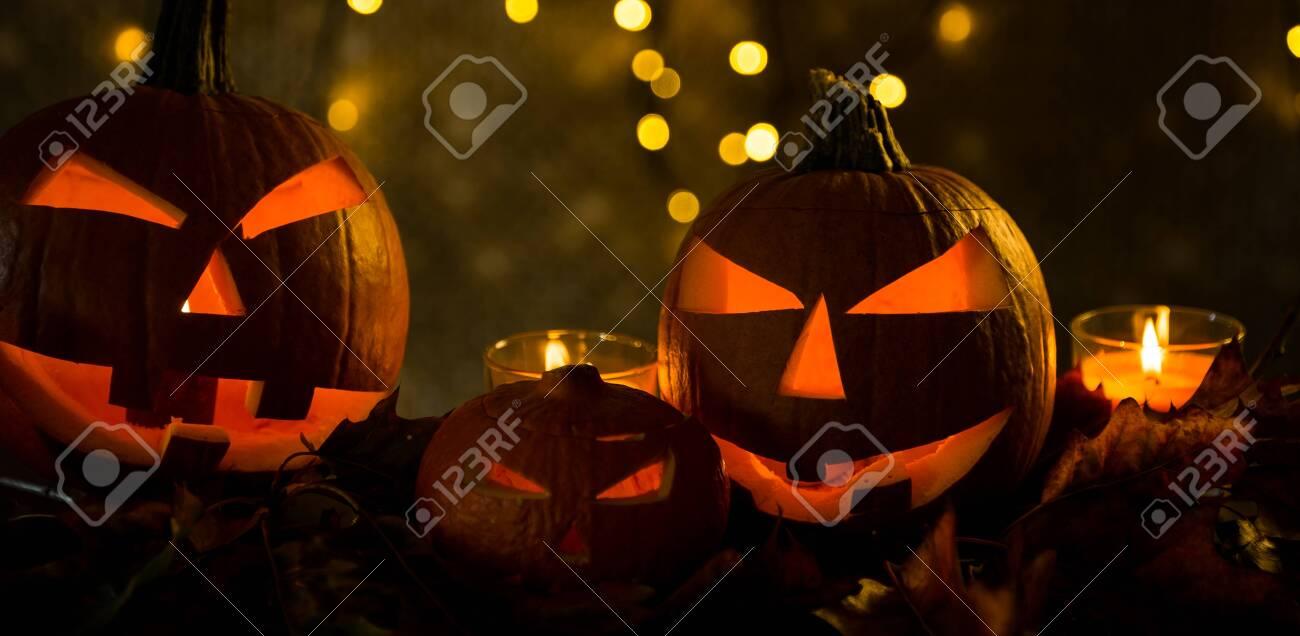 Halloween pumpkin head jack lantern with burning candles in scary deep night - 141471263