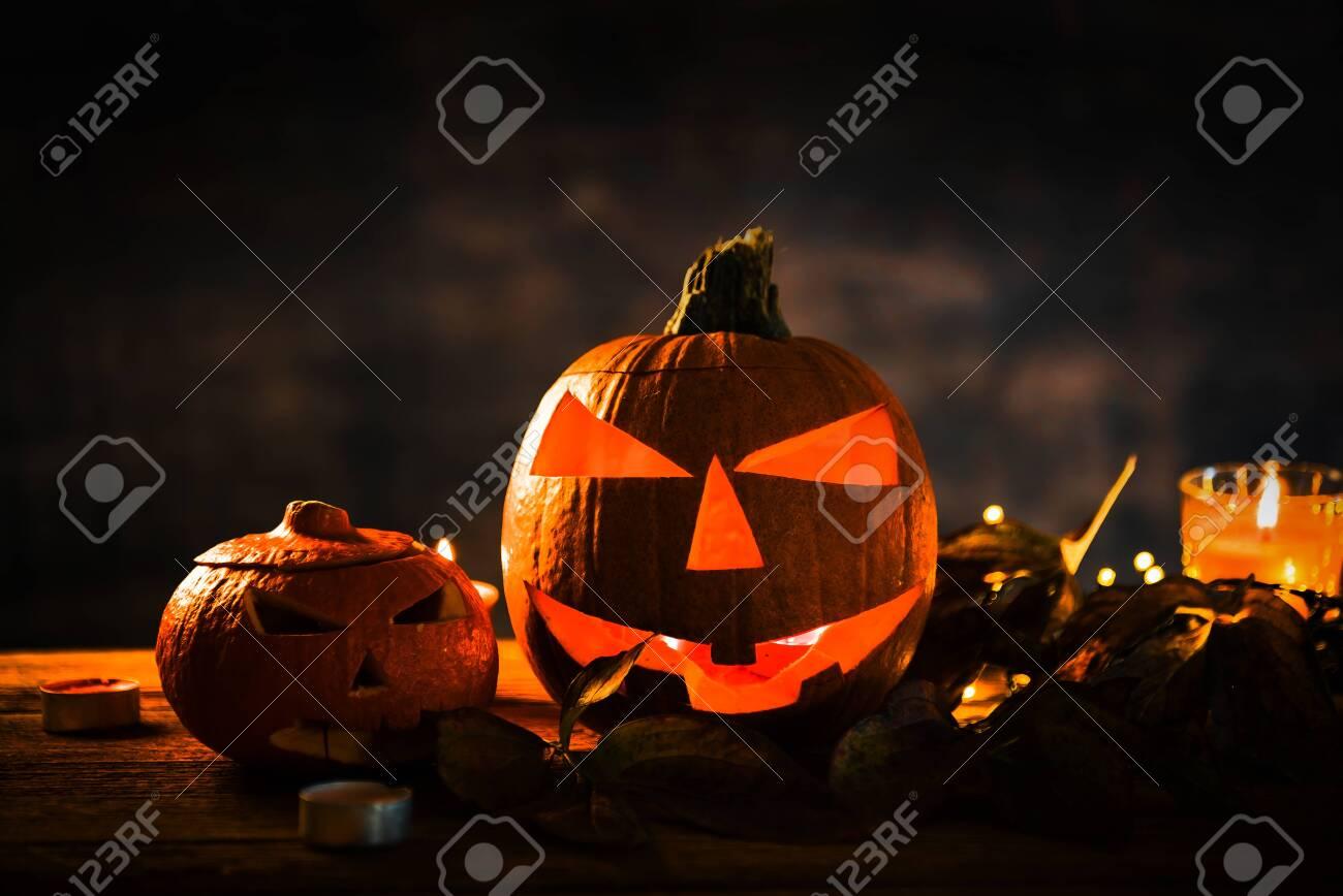 Halloween pumpkin head jack lantern with burning candles in scary deep night - 141471265