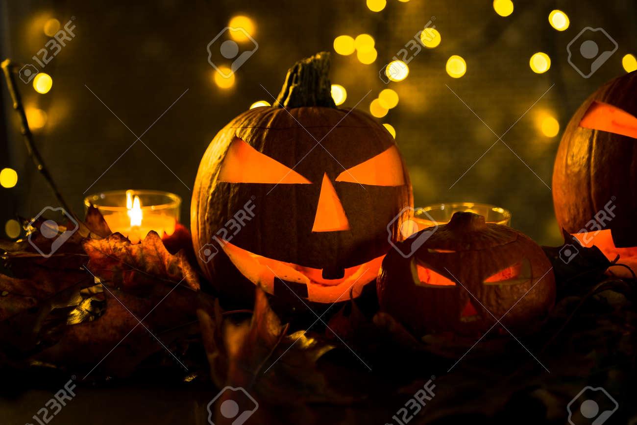 Halloween pumpkin head jack lantern with burning candles in scary deep night - 141471273
