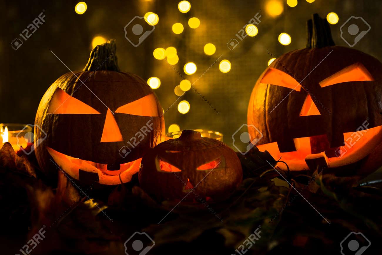 Halloween pumpkin head jack lantern with burning candles in scary deep night - 141471275