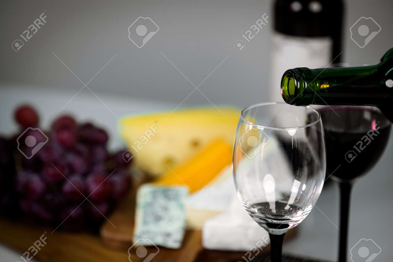 Pouring red wine from a bottle into a wineglass: wine tasting and celebration - 144316218