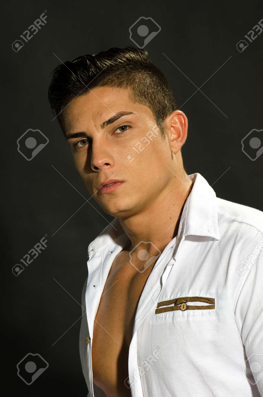 Portrait of young man with unbuttoned shirt against black background Stock Photo - 16655854
