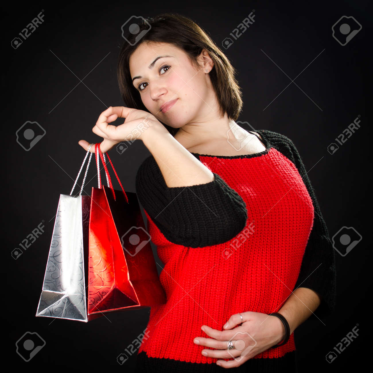 Portrait of young woman with gift bags against black background Stock Photo - 17866300