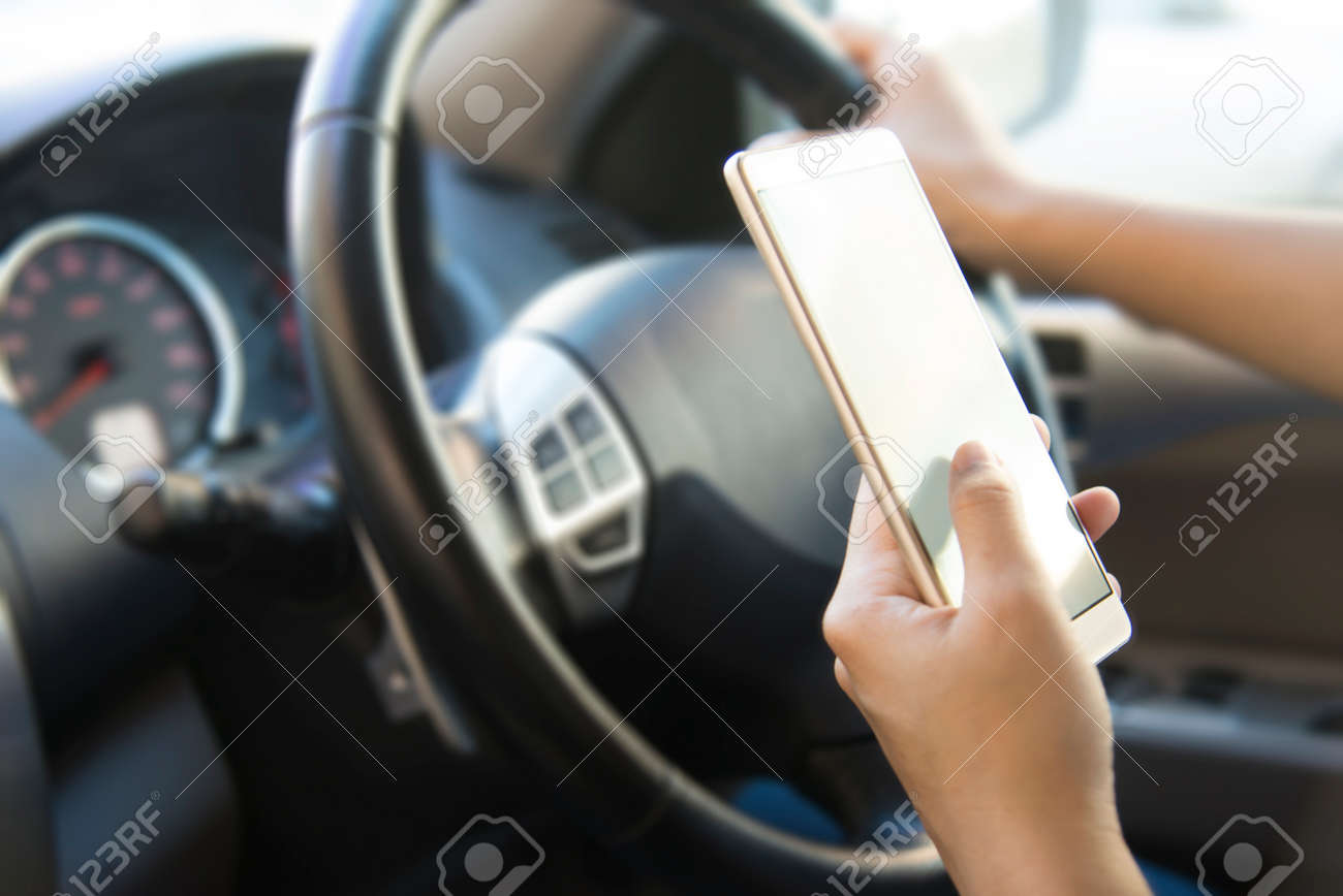 Woman Using Her Smartphone Gps While Driving. Blurred Car Interior on