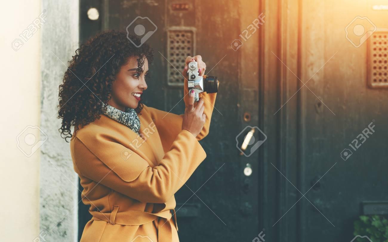 Concentré Beau Amateur Femelle Bouclé Professionnel Photographe En Jaune à  La Mode Manteau Photo De Tir Pour Le Journal En Utilisant Un Appareil Photo  ...