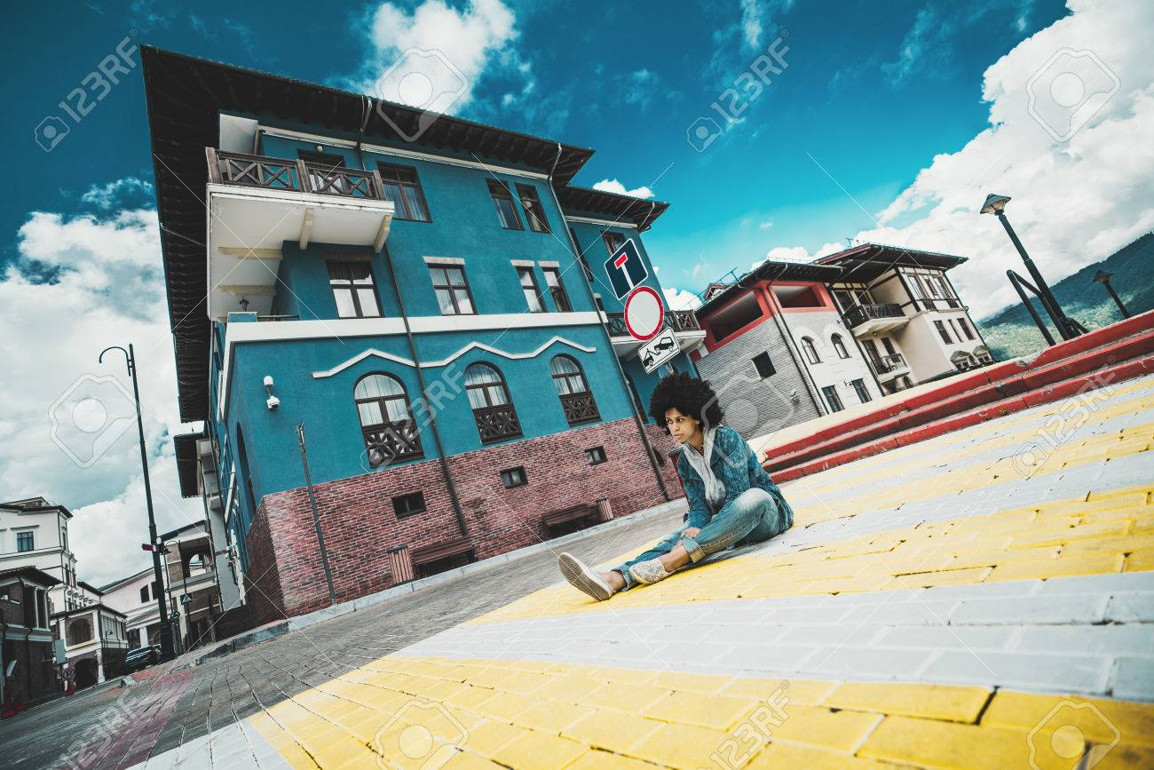 Wide-angle view of pensive black girl sitting on the paving stones right on the crosswalk of urban street on sunny autumn day with resort buildings in the background, Estosadok district, Sochi, Russia Foto de archivo - 87332585
