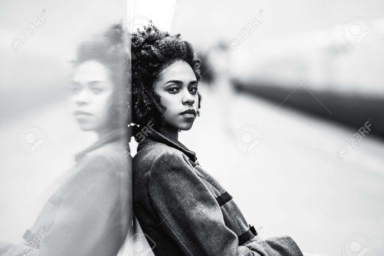 Black and white portrait of charming african american female in the coat leaning against a mirror wall the greyscale shot of a cute black teenage girl