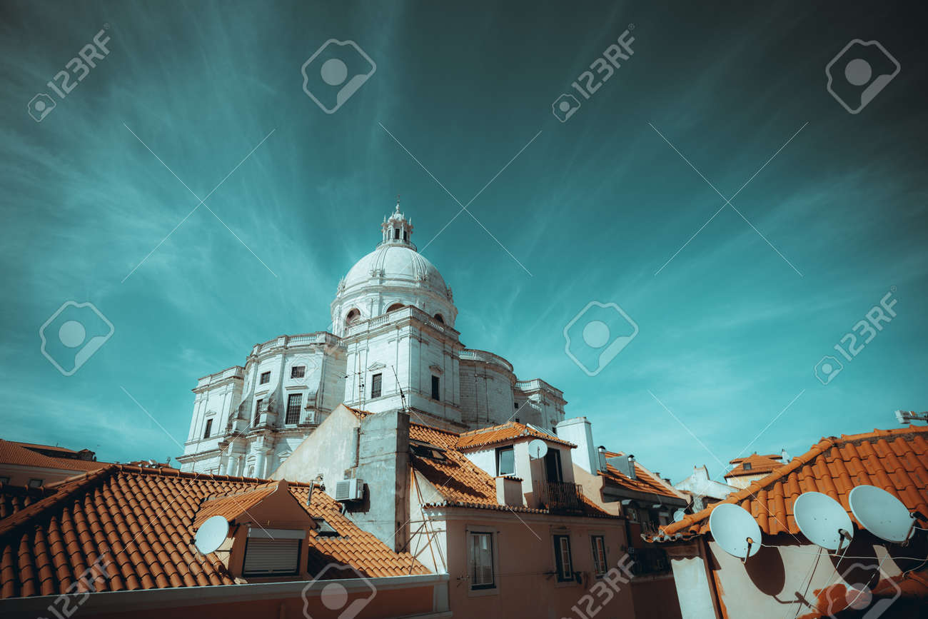 A wide-angle cityscape of a residential district of Lisbon, Portugal with a The Church of Santa Engracia or another name National Pantheon, with a cloudscape in the form of diverging emanations - 165106020