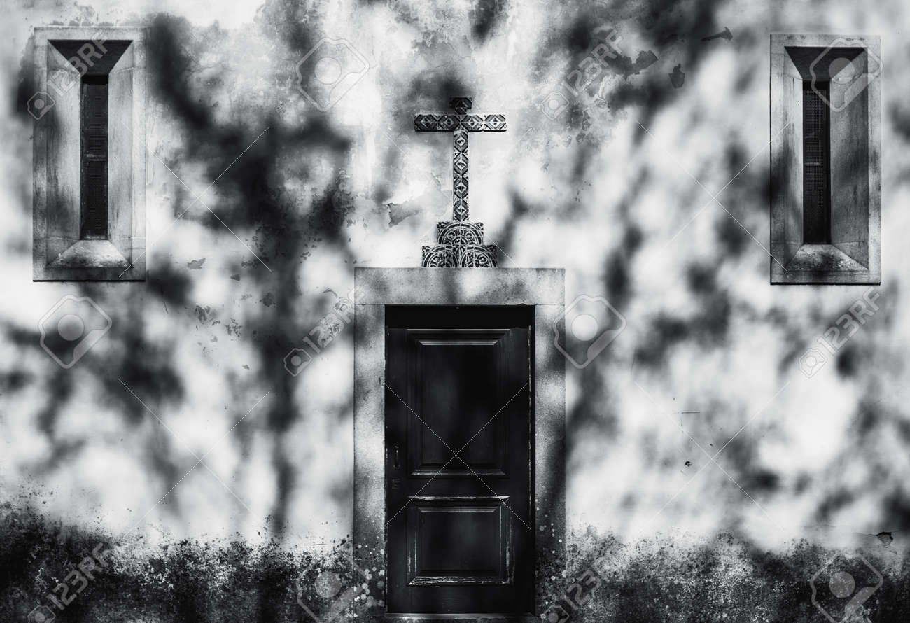 Black and white symmetrical shot of a small wooden church door with a ceramic tiled religious cross over it and two narrow windows on sides, a shadow of tree projecting on the wall like emanations - 167225210
