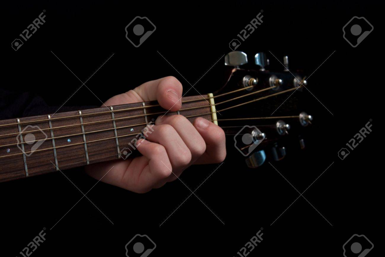 The Neck Of An Acoustic Guitar With Fingers Placed On A Chord Stock