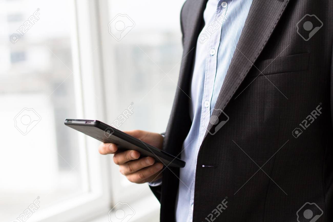 Businessman using tablet pc and works on it Stock Photo - 18298331