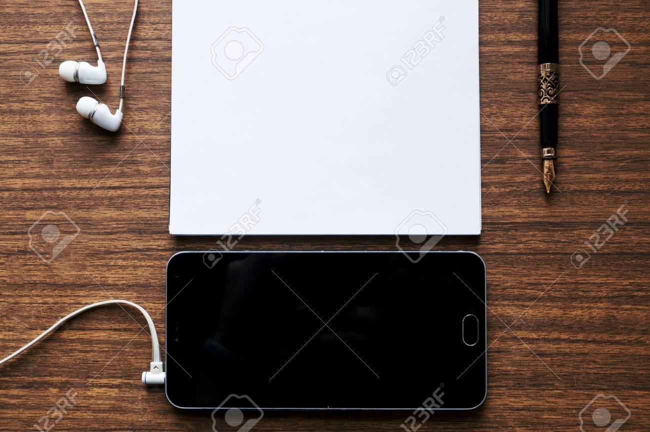 Casque téléphone stylo sur fond de table bureau en bois rouge