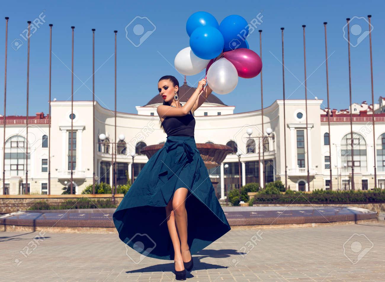 fd719b31e1 Foto de archivo - Retrato de moda de mujer joven y glamour en el vestir  elegante y bijou celebración de globos de colores