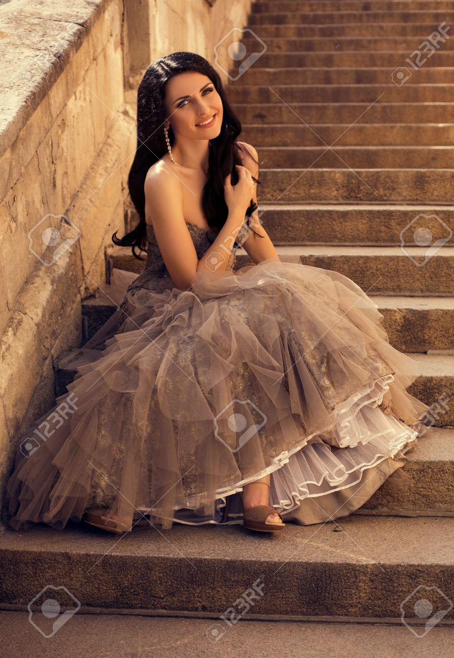 a6e7b48e01ef Foto de la manera de la mujer hermosa del encanto en alineada de lujo un  poco con la joyería sienta en las escaleras en el parque