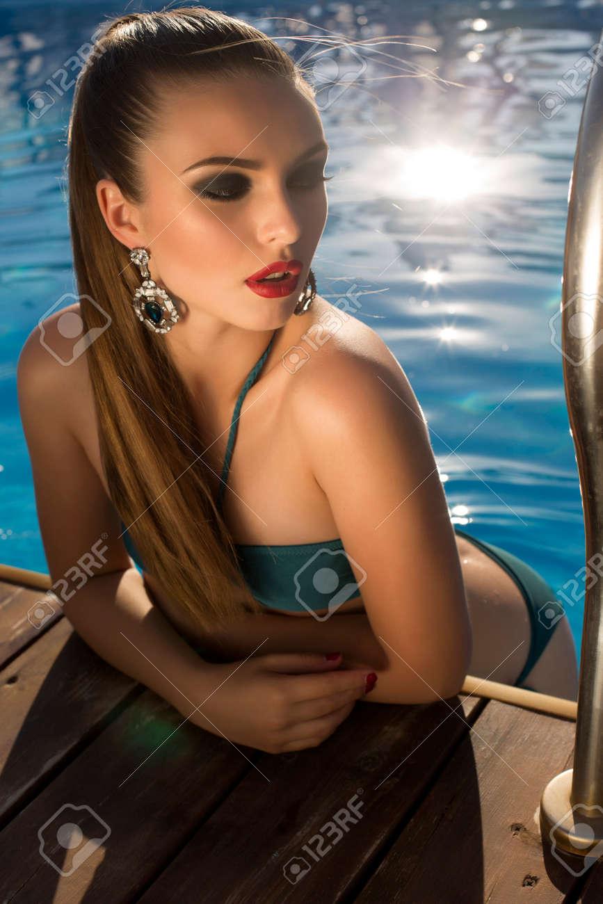 fashion photo of beautiful glamour brunette in bikini with bijou