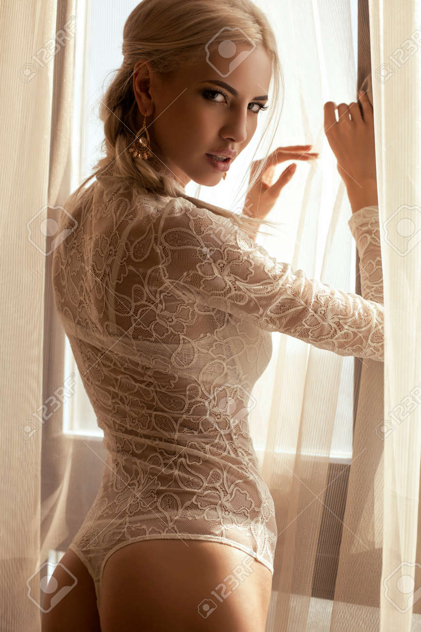 portrait of beautiful girl with blond hair in white lace lingerie posing  beside a window at