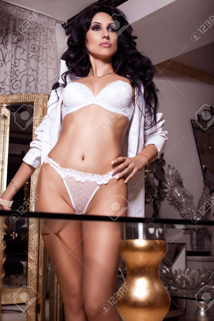 Foto De La Moda De Mujer Sexy Con El Pelo Negro En La Ropa Interior Blanca Y Una Túnica Que Presenta En El Dormitorio