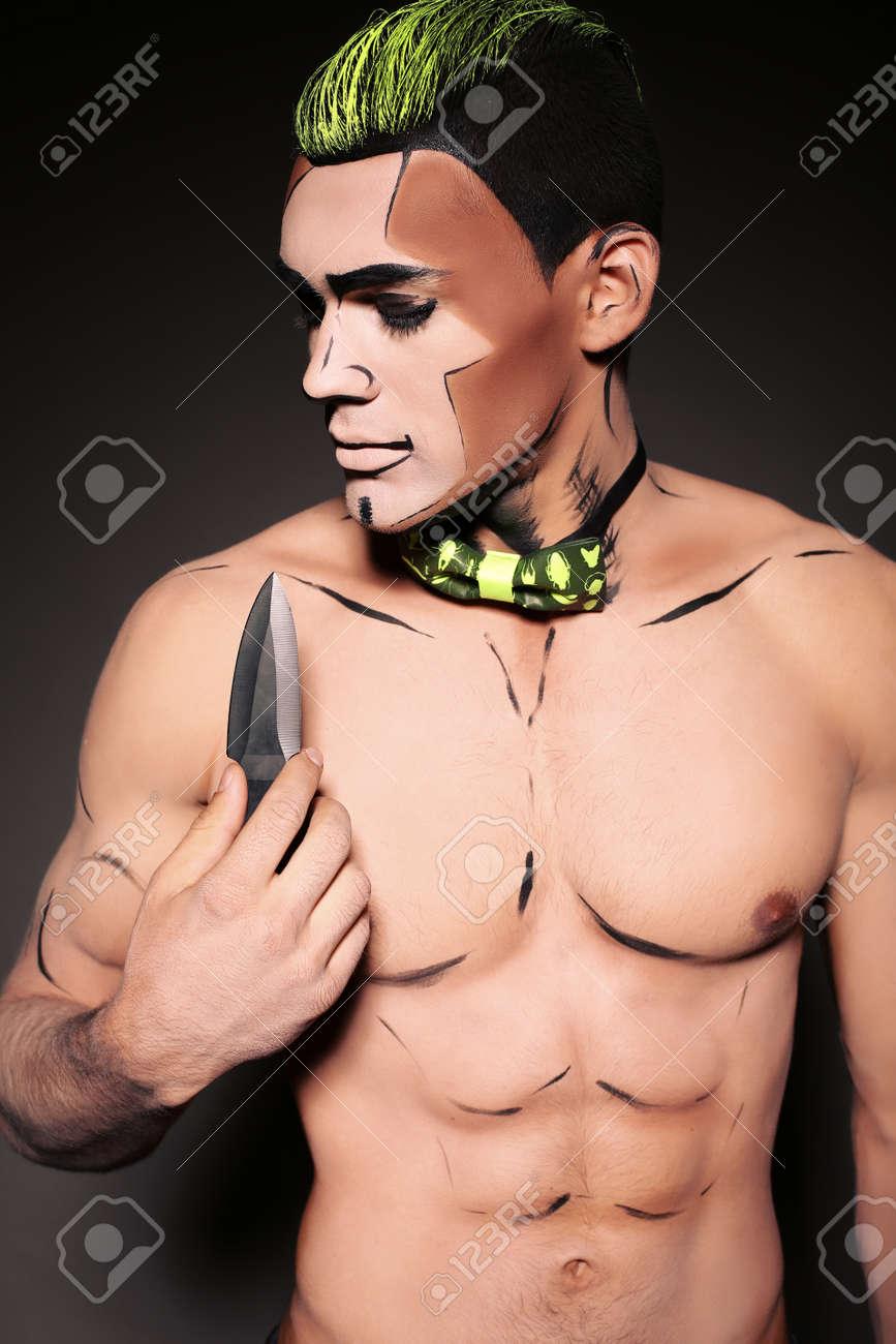 Foto de archivo , estudio de la moda de hombre musculoso sexy con la cara pintada para la fiesta de Halloween