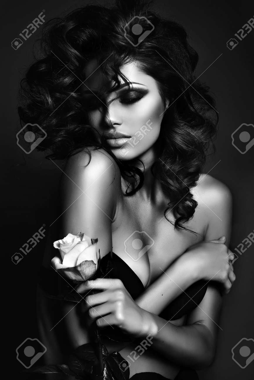 Black and white fashion photo of beautiful sexy woman with luxurious curly hair in elegant lingerie