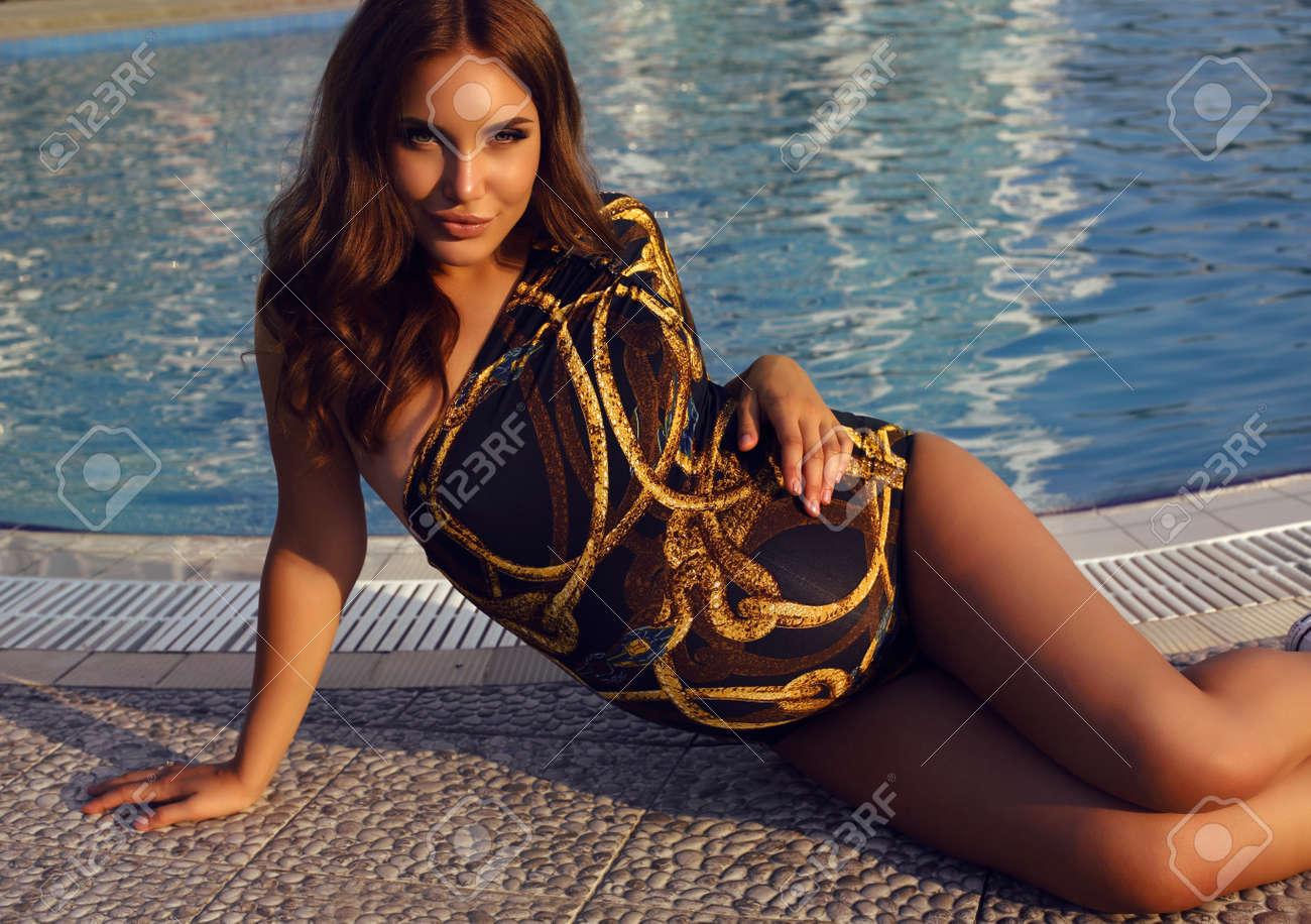 a97ee6bd7f5e Entre la foto de la mujer embarazada hermosa con el pelo oscuro en traje de  baño elegante que presenta al lado de la piscina