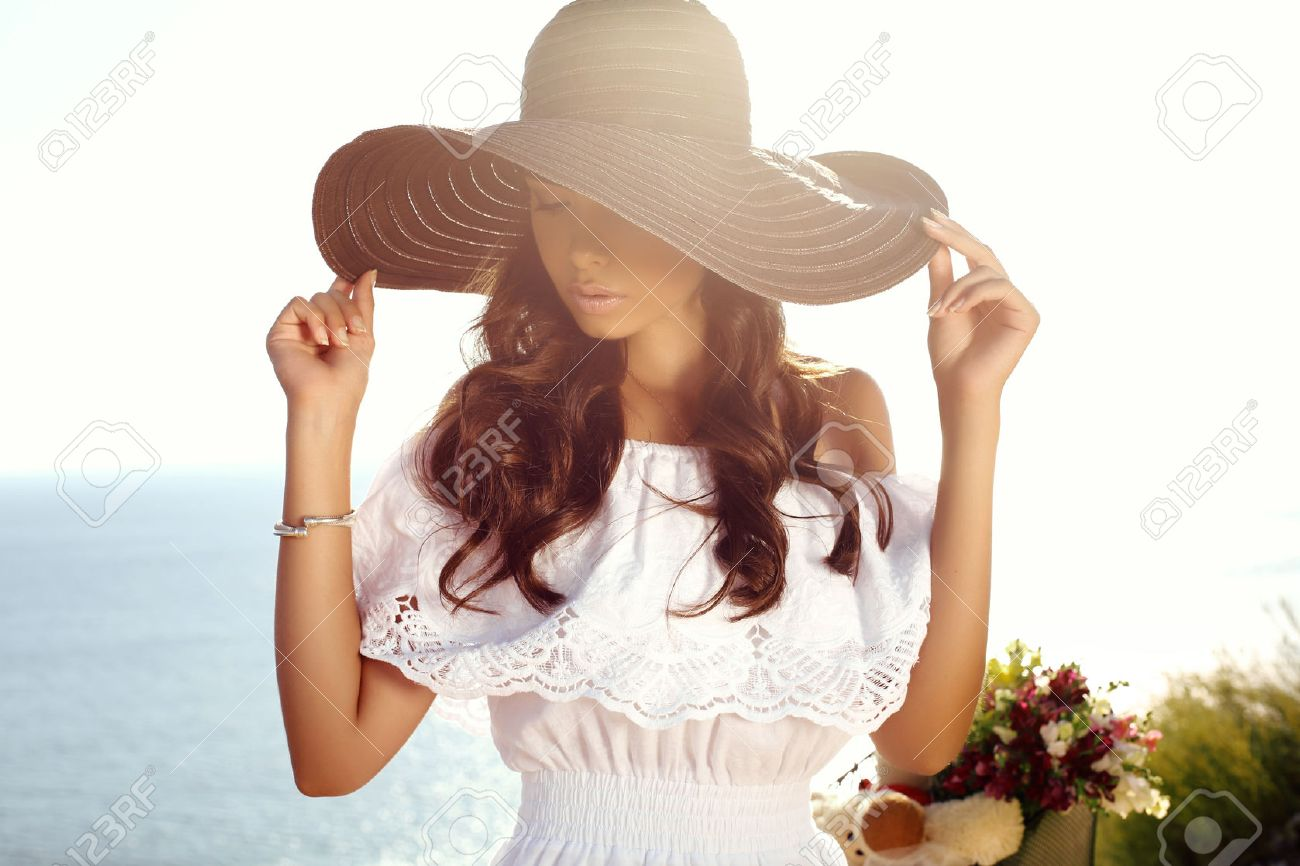 fashion outdoor photo of beautiful sensual girl with dark hair in elegant dress and hat riding by summer beach - 48829706