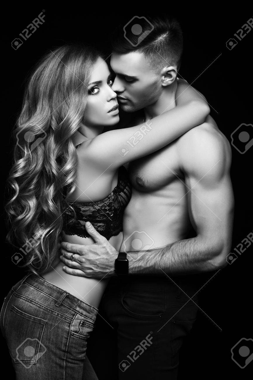 Fashion black and white studio photo of beautiful couple with sportive sexy bodies gorgeous woman
