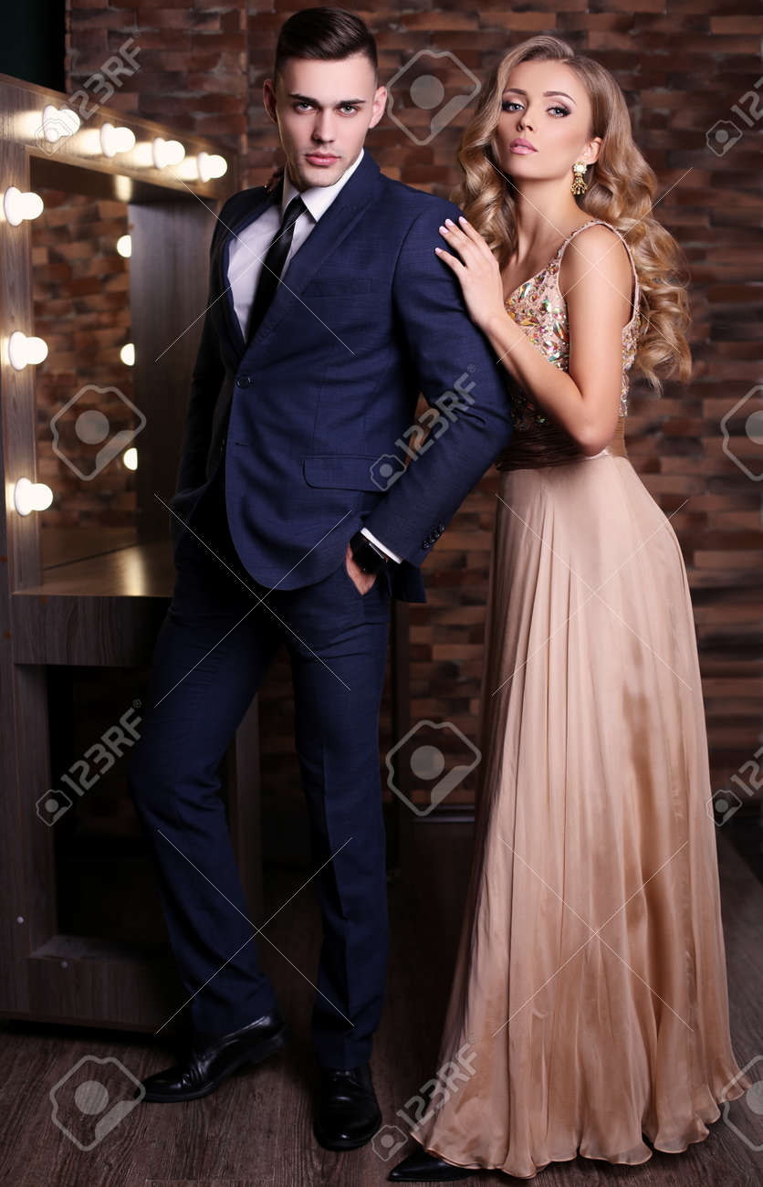 fashion studio photo of beautiful couple in elegant clothes, gorgeous woman with long blond hair embracing handsome brunette man - 51693334