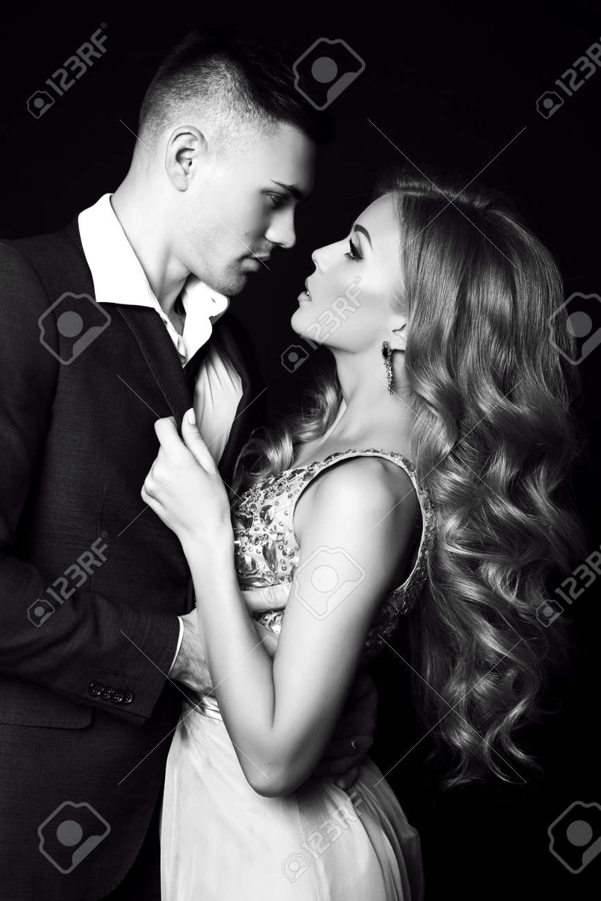 Fashion black and white studio photo of beautiful couple in elegant