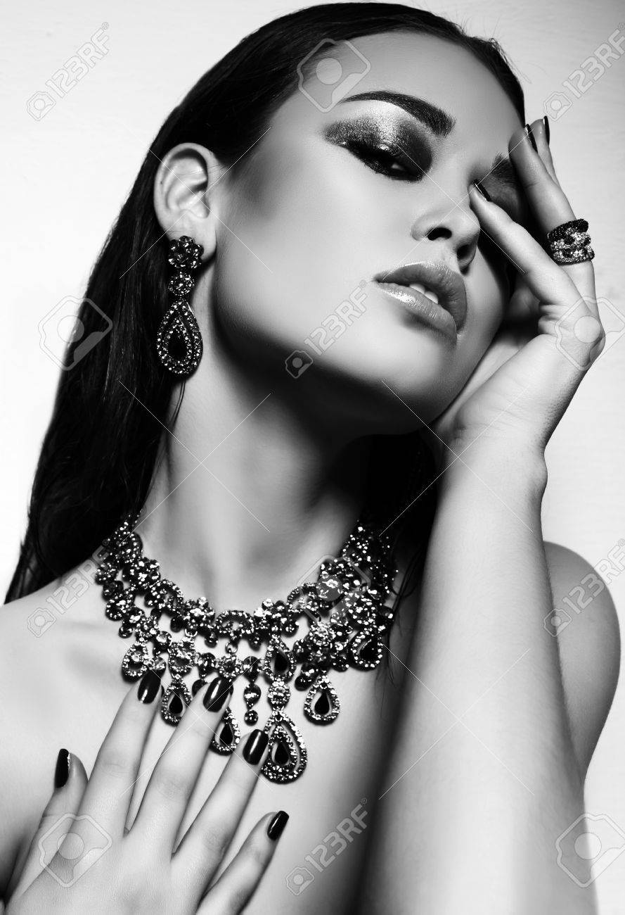 Fashion studio black and white photo of gorgeous sexy woman with dark hair and bright makeup