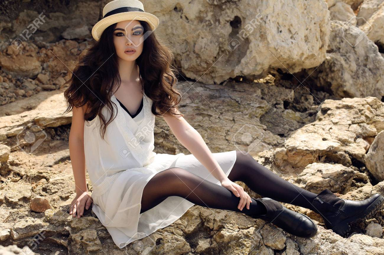 fashion outdoor photo of beautiful girl with dark hair wears casual elegant clothes and hat posing at summer seacoast - 55374811