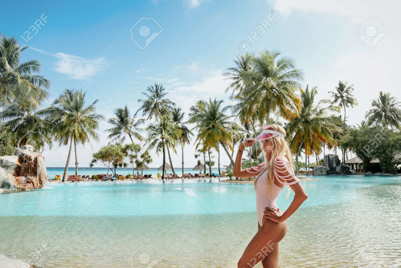 fashion outdoor photo of beautiful woman with blond hair in elegant beach clothes relaxing in Maldive island - 102072704