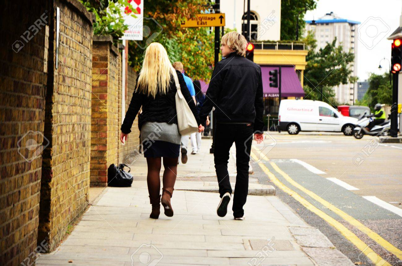 A young couple is walking on the street, holding hands. - 12201434