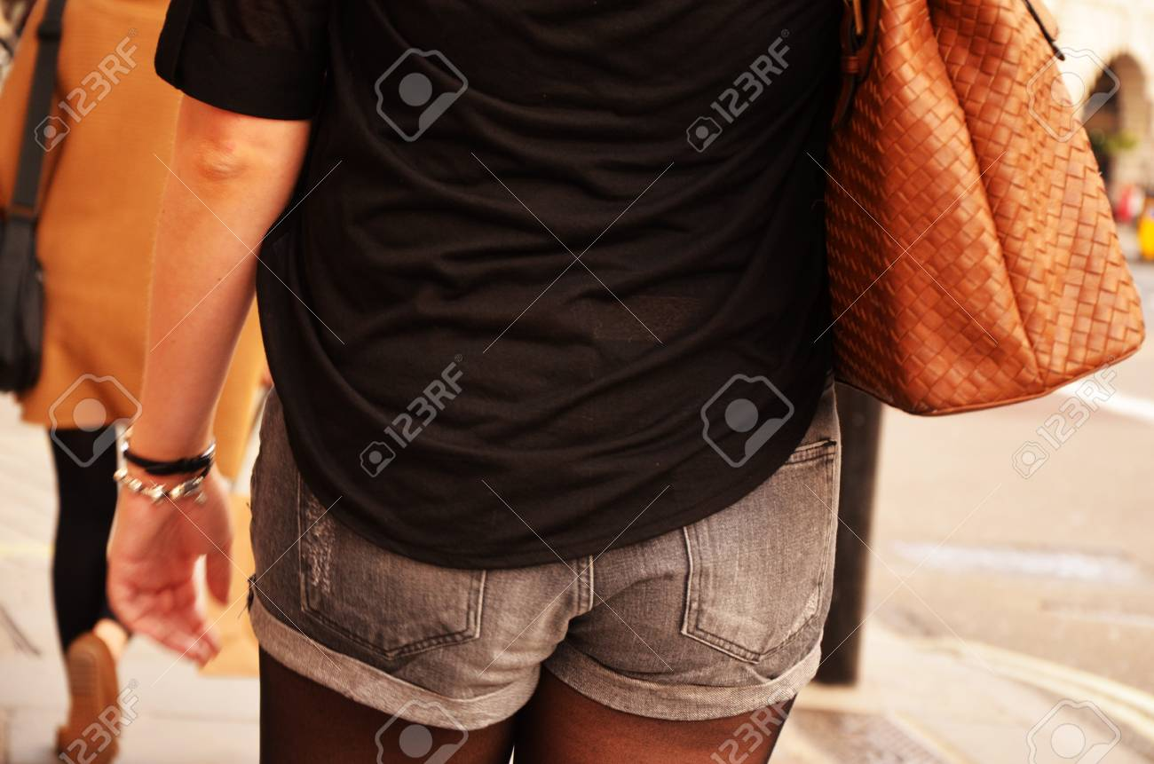 A hot girl is wearing shorts and is equipped with a stylish handbag - 15763134