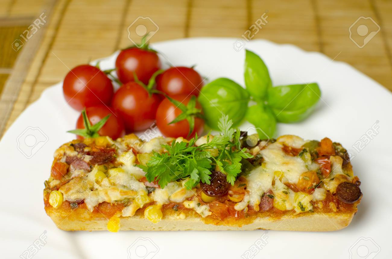 A close-up of baguette pizza on a white plate with vegetables in the background. Shallow depth of the field. - 14646835