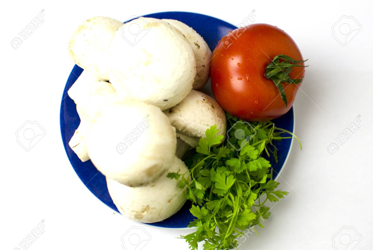 A bunch of mushrooms, a tomato and parley are on placed on a blue plate. Shallow depth of the field. - 14646826