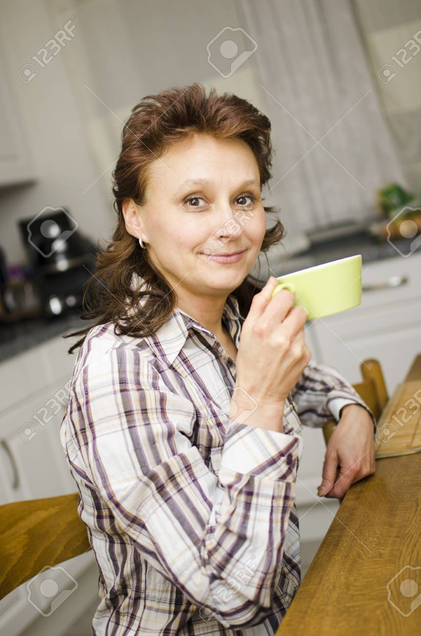 A woman is drinking coffee in the kitchen. - 17079596