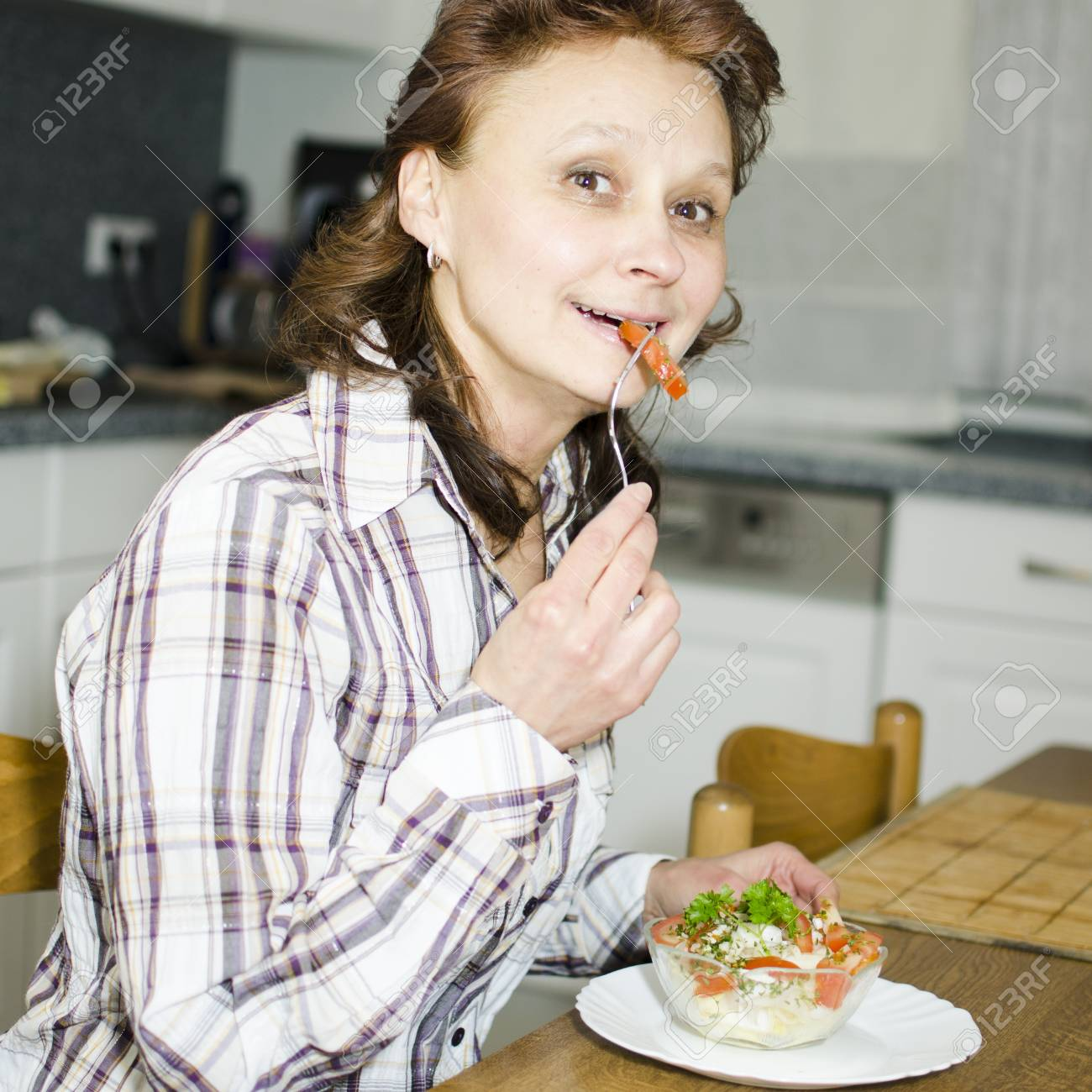 A woman is eating salad in the kitchen. - 17079591