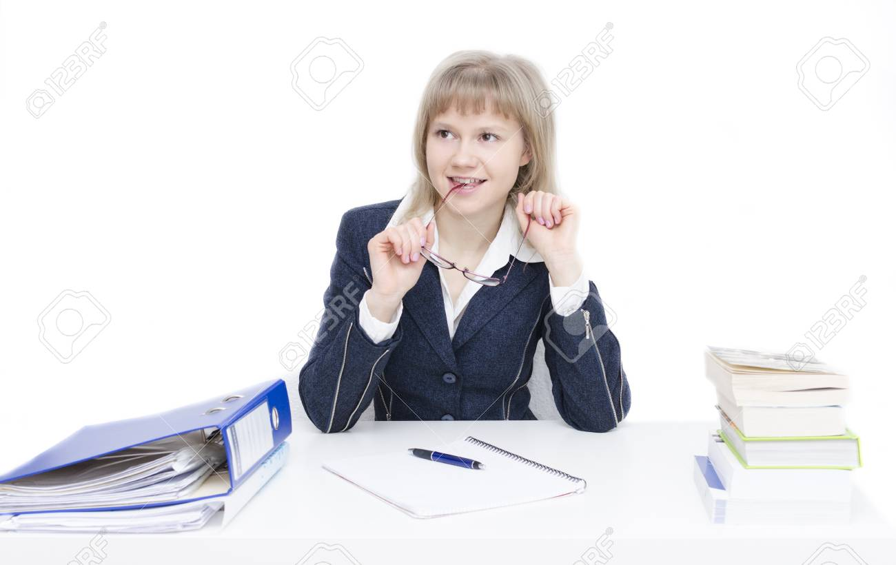 A young woman is sitting at the desk and is studying - 24703239